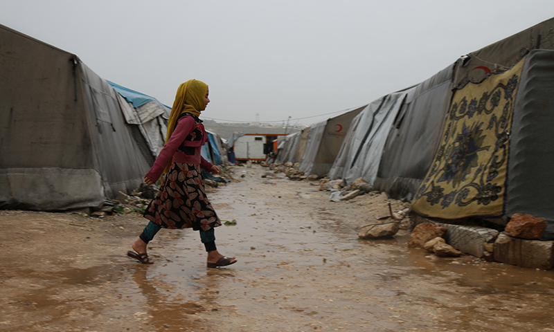 A child walking between the tents in Aleppo Labeeh camp during the first rainy day of Ramadan – 24 April 2020 (Enab Baladi)