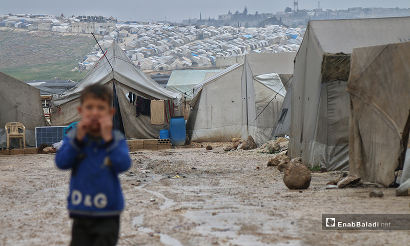 A child standing under the rain on the first day of Ramadan, while tents could be seen behind him in Aleppo Labeeh camp – 24 April 2020 (Enab Baladi)