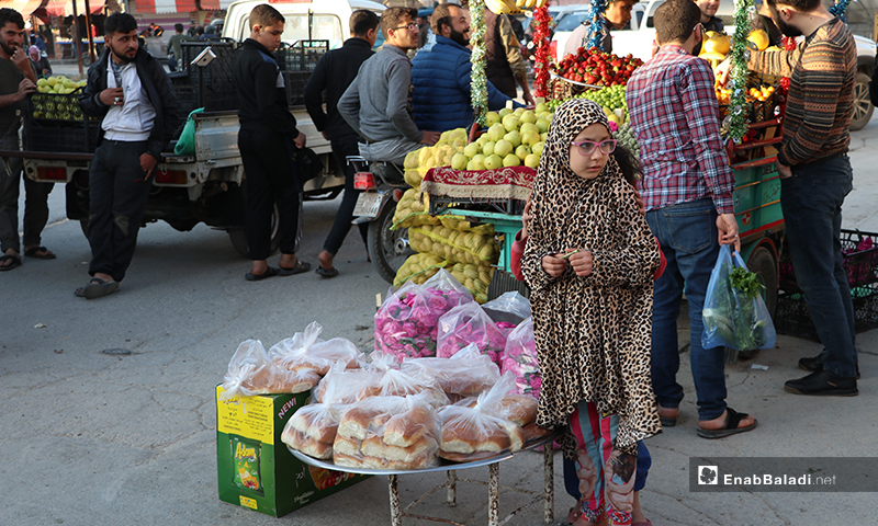 A child selling roses, maarouk bread, and licorice drink in al-Bab city in rural Aleppo – 26 April 2020 (Enab Baladi)