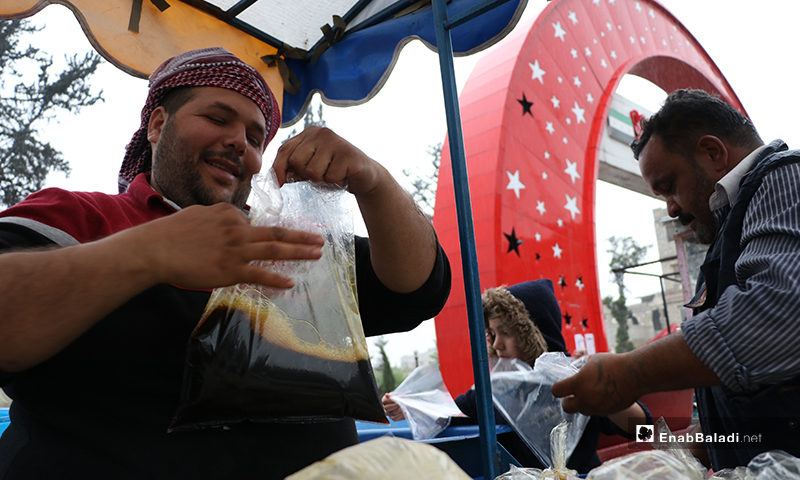 A street vendor putting licorice drink in bags in al-Bab city of rural Aleppo during the rainy Ramadan atmosphere – 24 April 2020 (Enab Baladi)