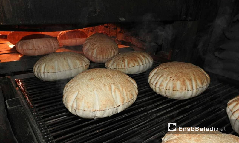 Syrian pita bread coming out of the fire stone oven in Dabiq bakery (Enab Baladi)