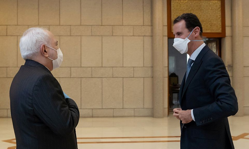 President of the Syrian regime Bashar al-Assad meets with Iranian Foreign Minister Mohammad Javad Zarif, both wearing protective face masks, in the Syrian capital Damascus - 20 April 2020 ( the Facebook page of the Presidency of the Syrian Arab Republic)