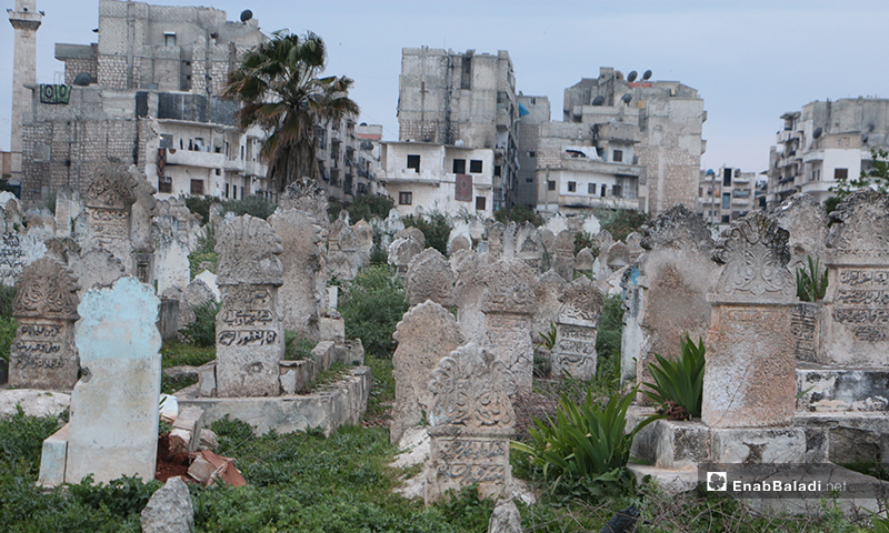 A graveyard in Idlib city ,residential buildings appear behind it - 15 April (Enab Baladi)