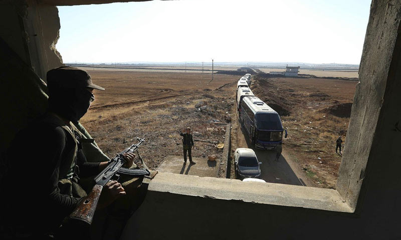A militant watching busses of Kefraya and al-Fouaa areas exiting the city - 17 July 2018 (afp)