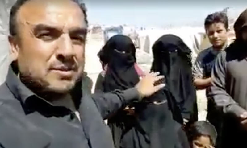 A man giving money rewards to Syrian girls for being veiled and asks a five-year-old child to wear a veil so that she can get a reward also - Idlib (Facebook activists' pages)