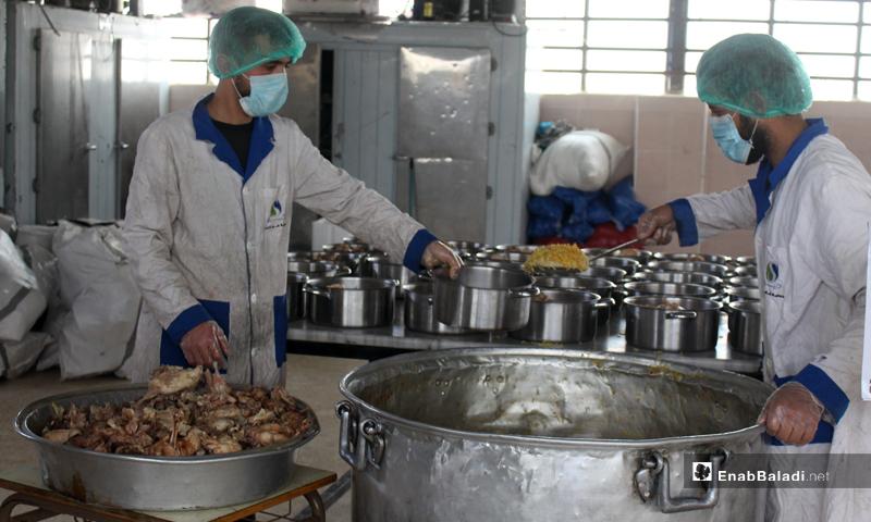 Aid workers distributing food baskets in a Ramadan kitchen in Idlib - 1 May 2020 (Enab Baladi)