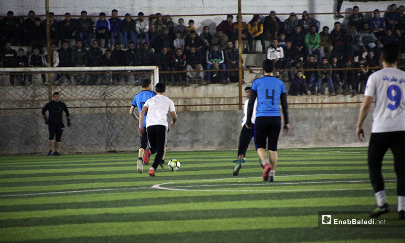 Two players trying to control the ball in the final match of the North Stars League between Deir Hassan and Akrabat teams in Kah area in Idlib – 03 May 2020 (Enab Baladi)