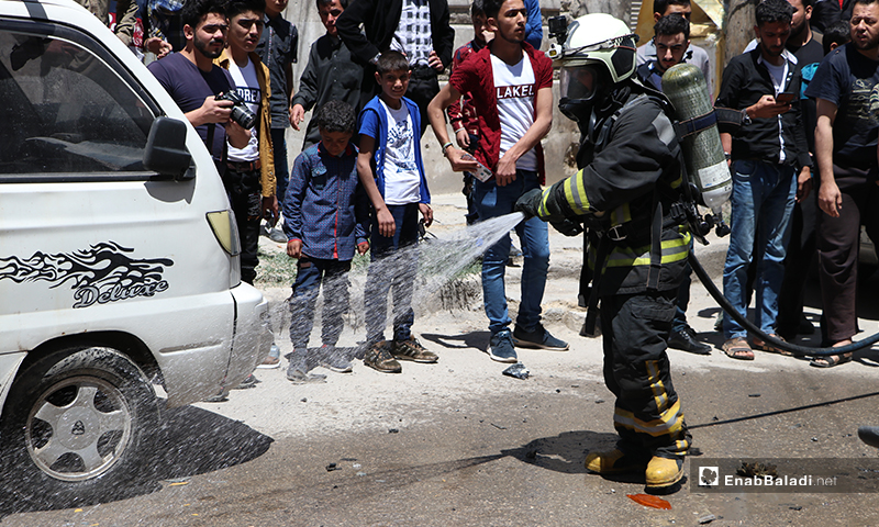 """Member of the Syrian Civil Defense and the residents at the improvised explosive device (IED) explosion site that targeted the vehicle of a member of the """"Sultan Murad"""" Division, affiliated to the Turkey-backed Syrian National Army (SNA) in al-Bab city, in the north-eastern countryside of Aleppo province – 25 May 2020 (Enab Baladi / Asim Melhem)"""