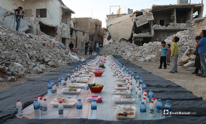 A row of dining iftar table set up amid heaps of rubble and destruction for the residents of Atarib city in rural Aleppo - 8 May 2020 (Enab Baladi)