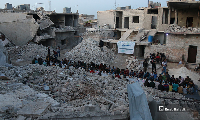 Residents of Atarib city in rural Aleppo gathering for a public iftar, surrounded by grey destruction and rubble - 8 May 2020 (Enab Baladi)