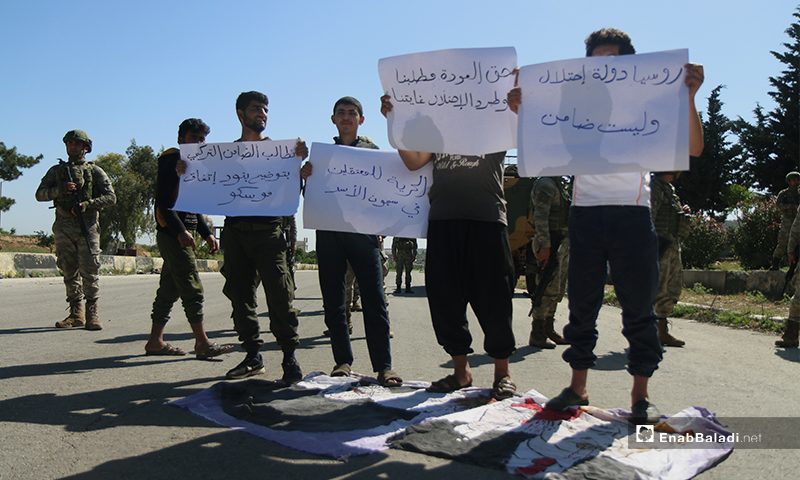 """Sit-in protesters on the Aleppo – Lattakia international""""M4"""" highway, raising signs condemning the passage of the military vehicles of the Russian – Turkish joint patrol on the road controlled by the opposition – 14 May 2020 (Enab Baladi)"""
