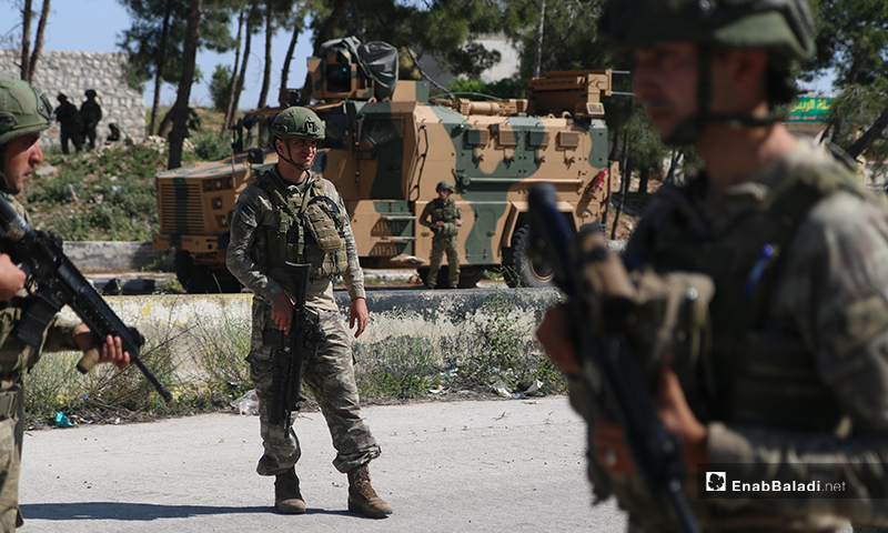 """Members of the Turkish Army Forces (TAF) standing near a military vehicle while being deployed on the Aleppo – Lattakia international """"M4"""" highway during the eleventh Russian-Turkish joint patrol – 14 May 2020 (Enab Baladi)"""