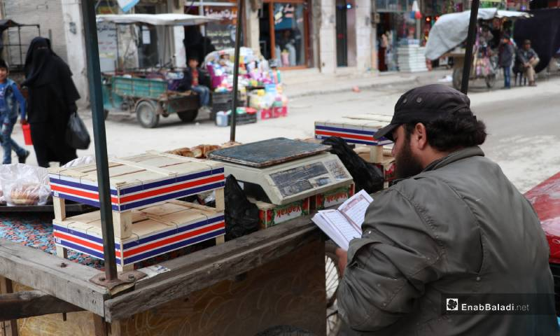 A vendor reading the Holy Quran in front of his street cart in one of the popular markets in al-Bab city – 04 May 2020 (Enab Baladi)