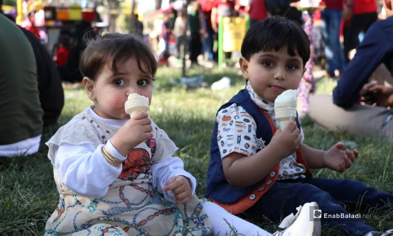 """Two children eating ice cream in """"al-Shaab"""" park at the center of al-Bab city – 26 May 2020 (Enab Baladi)"""