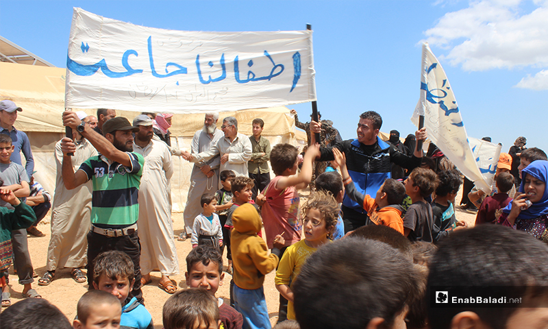 Displaced Syrian children in al-Omran camp, west of Haranabush, demonstrating because of the lack of food, water, bread, and access to essential services - 10 May (Enab Baladi)