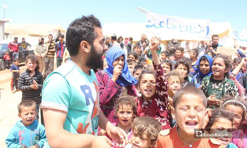 """Displaced Syrian children in the al-Omran camp, west of Haranabush during the demonstration, which took place to demand the provision of basic necessities of life, and behind them a banner, saying """"Our children are starving"""" - 10 May (Enab Baladi)"""