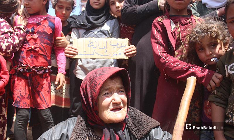An old woman, children standing behind her, demonstrating near the al-Omran camp, west of Haranabush - 10 May (Enab Baladi)