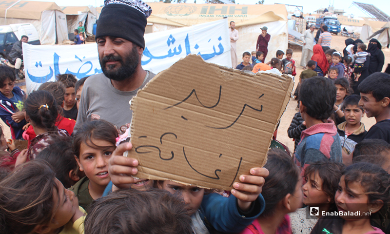"""A displaced child holding a banner reading, """"We need relief needs,"""" in the demonstration of al-Omran camp, west of Haranabush - 10 May (Enab Baladi)"""