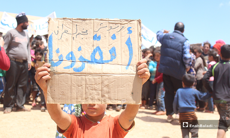 """A displaced child carrying a cartoon banner reading, """"Save us please,"""" during a demonstration for the displaced people of the al-Omran camp, west of Haranabush - 10 May (Enab Baladi)"""