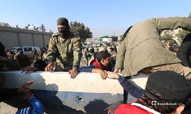 Members of Hay' at Tahrir al-Sham (HTS) preventing protesters from reaching Bab al-Hawa crossing which links Turkey with northern rural Idlib - 20 December 2019 (Enab Baladi)