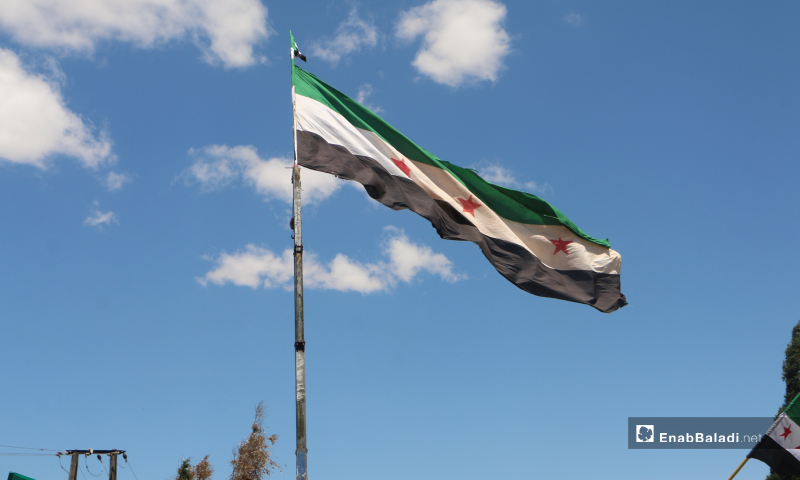 "The Syrian independence flag was raised in the demonstration held under the slogan the ""Flood of Return"" and organized by activists on the road between Idlib and Sarmin – 25 May 2020 (Enab Baladi / Anas al-Khouli)"