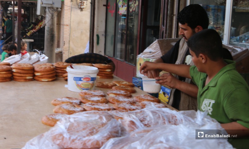 A street vendor sprinkles coconut shreds on the Maarouk bread, one of Ramadan's famous and popular delights in Marea city of Aleppo countryside – 20 May 2020  (Enab Baladi - Abdul al-Salam Majaan)