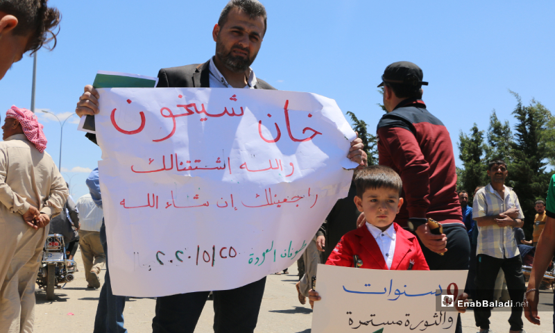 "An activist and a child raised banners in the demonstration held under the slogan the ""Flood of Return"" on the second day of Eid al-Fitr on the road between Idlib and Sarmin. The activist"