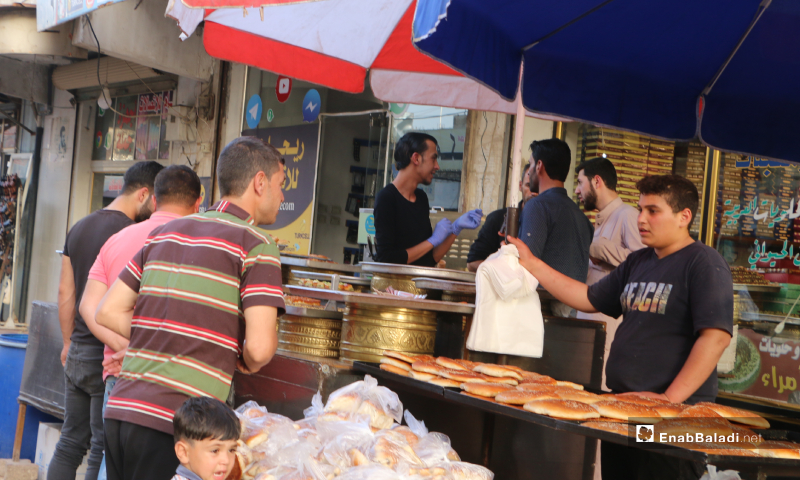 Residents buying the Maarouk bread, one of Ramadan's famous and popular delights from a sweets shop in Marea city of Aleppo countryside – 20 May 2020  (Enab Baladi - Abdul al-Salam Majaan)