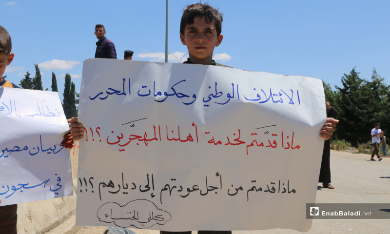 "A child raised a banner in the demonstration held under the slogan the ""Flood of Return"" on the second day of Eid al-Fitr on the road between the cities of Idlib and Sarmin. The banner reads, "" The National Coalition and governments of the liberated areas, what have you offered to serve our displaced people?! What have you offered to help to return the displaced to their homes?!"" – 25 May 2020 (Enab Baladi / Anas al-Khouli)"