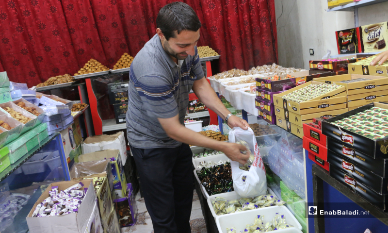 A sweet seller displaying Eid al-Fitr's sweets in one of the shops in Marea city of Aleppo countryside – 20 May 2020  (Enab Baladi - Abdul al-Salam Majaan)