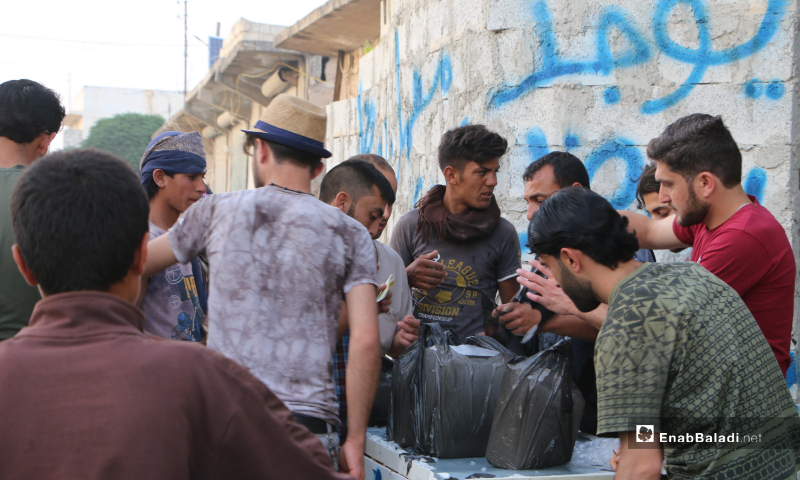 A group of young men buying large ice cubes, which became popular with the rising temperatures – 20 May 2020  (Enab Baladi - Abdul al-Salam Majaan)