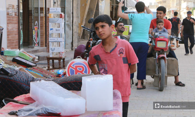 A child standing beside a street cart selling large ice cubes, which witnessed a great demand after the rising temperatures – 20 May 2020  (Enab Baladi - Abdul al-Salam Majaan)