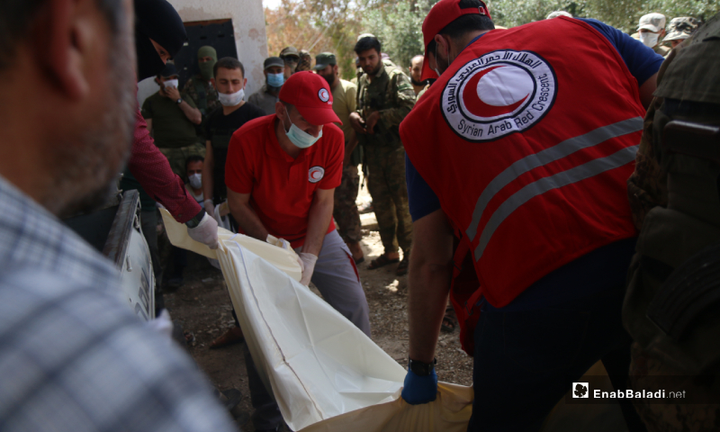 Members of the Syrian Arab Red Crescent (SARC) putting the dead body of one of the regime's killed elements in a plastic bag during the prisoners' exchange process between the Syrian regime and the HTS – 16 May 2020 (Enab Baladi / Yousef Ghuraibi)