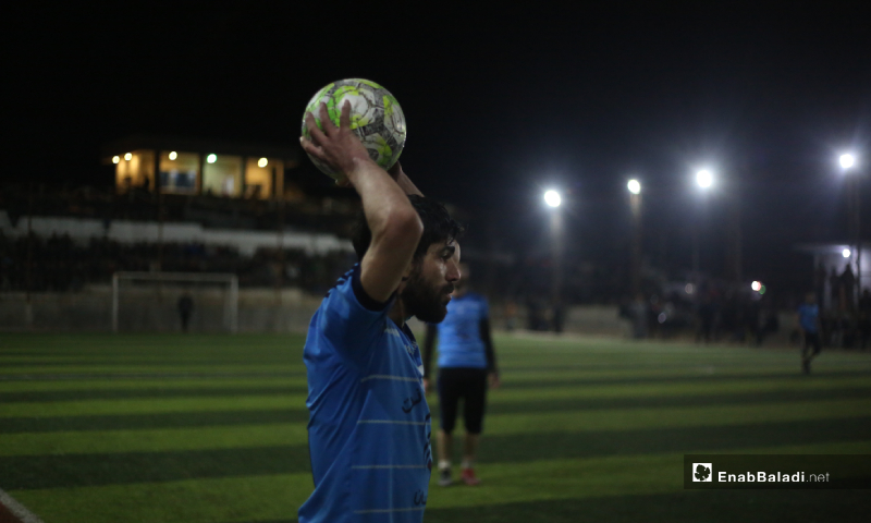 A football player performing a throw-in at the final match of the North Stars League between Deir Hassan and Akrabat teams in Kah area in Idlib – 03 May 2020 (Enab Baladi)