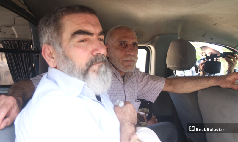 Prisoners of Syrian regime forces waiting in the car before being driven to the exchange location during the prisoners' exchange process between the Syrian regime and the HTS – 16 May 2020 (Enab Baladi / Yousef Ghuraibi)