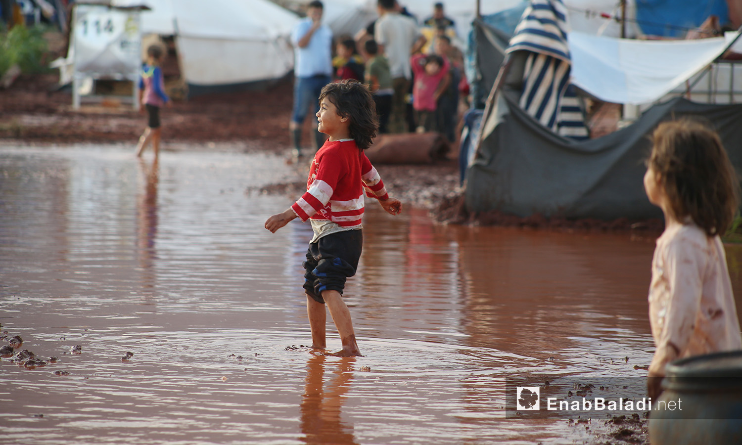 """A child whose feet are covered by water due to the rainstorm that hit """"Sahl al-Khair"""" camp for Syrian internally displaced people (IDPs) near Kafr Bunni in northern Idlib countryside – 19 June 2020  (Enab Baladi / Yousef Ghuraibi)"""