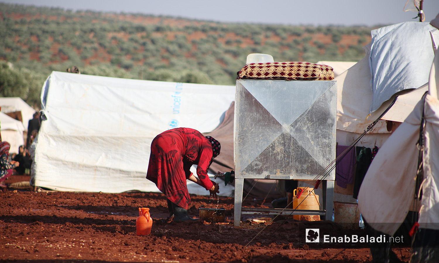 """A woman washing dishes at """"Sahl al-Khair"""" camp for Syrian internally displaced people (IDPs) after the rainstorm near Kafr Bunni in northern Idlib countryside – 19 June 2020  (Enab Baladi / Yousef Ghuraibi)"""