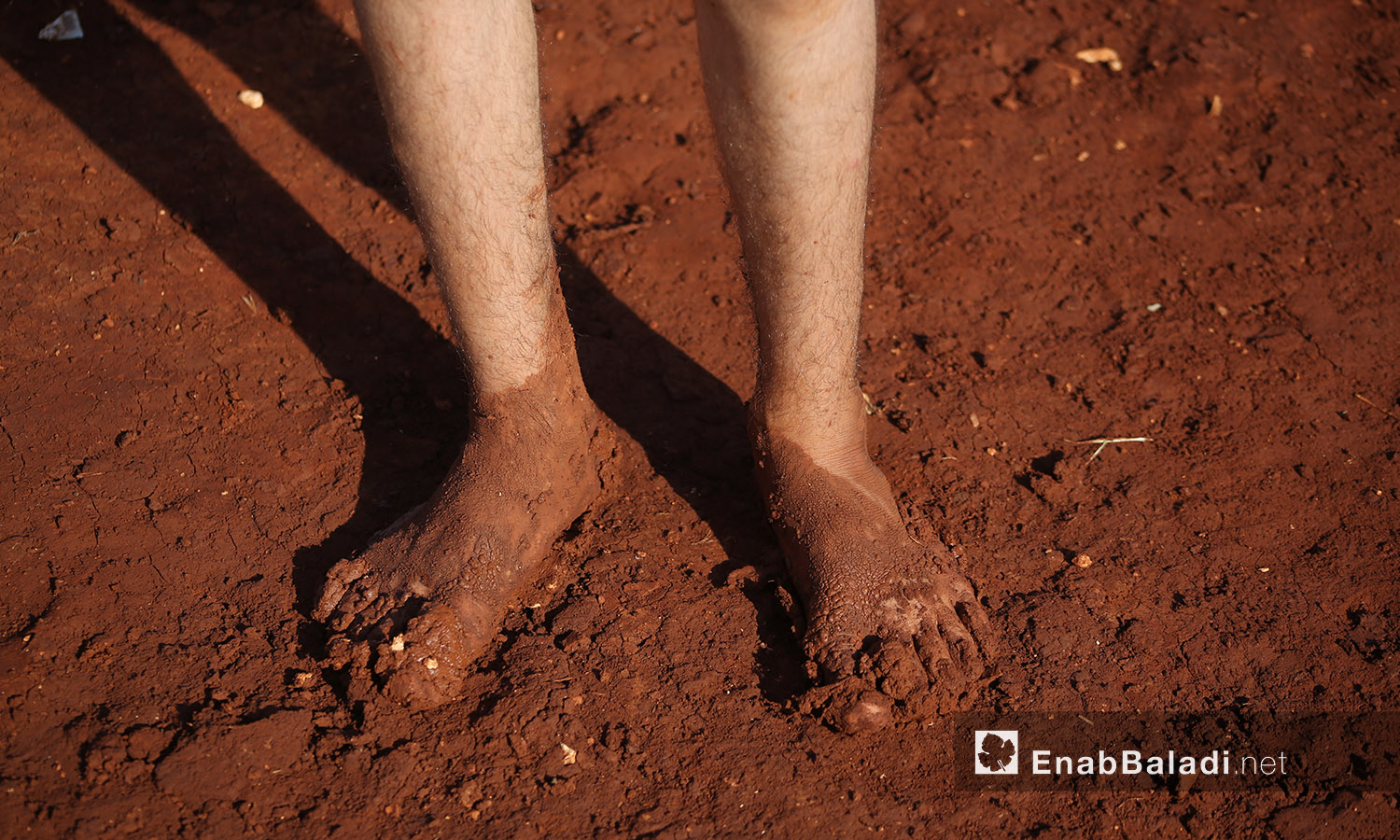 """A child's two feet covered with mud after the rainstorm that hit """"Sahl al-Khair"""" camp for Syrian internally displaced people (IDPs) near Kafr Bunni in northern Idlib countryside – 19 June 2020  (Enab Baladi / Yousef Ghuraibi)"""