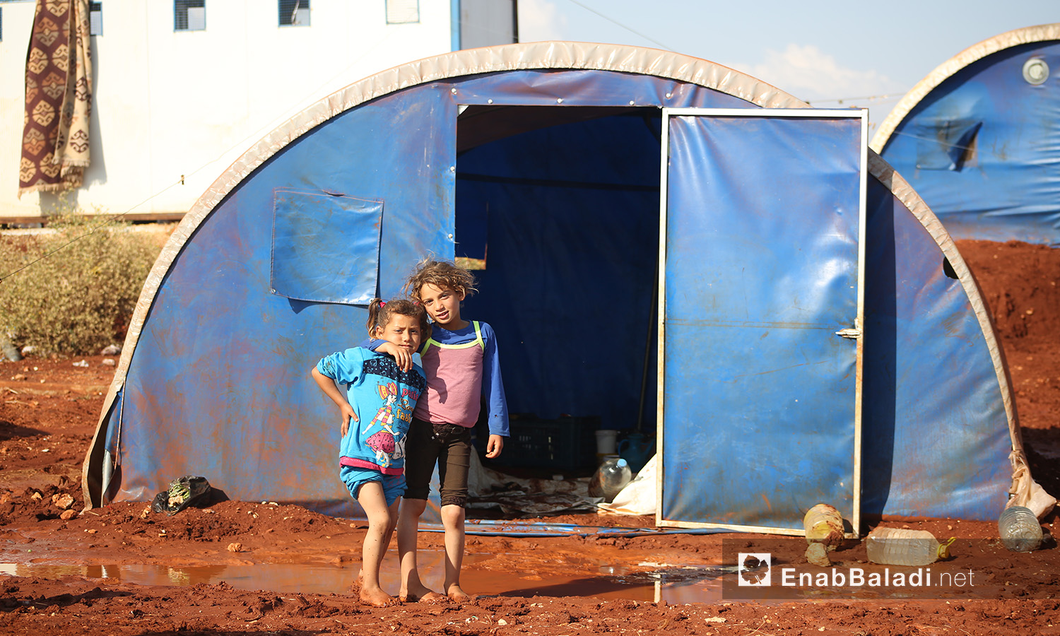 """Two children in front of their tent at """"Sahl al-Khair2 camp for Syrian internally displaced people (IDPs) after the rainstorm near Kafr Bunni in northern Idlib countryside – 19 June 2020  (Enab Baladi / Yousef Ghuraibi)"""