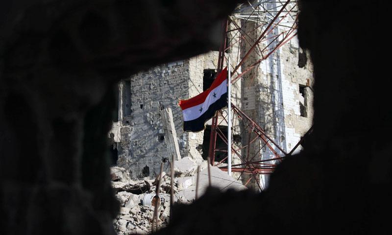 The Syrian regime's flag raised between the destroyed buildings of Daraa al-Balad neighborhood - 12 July 2018 (AFP)