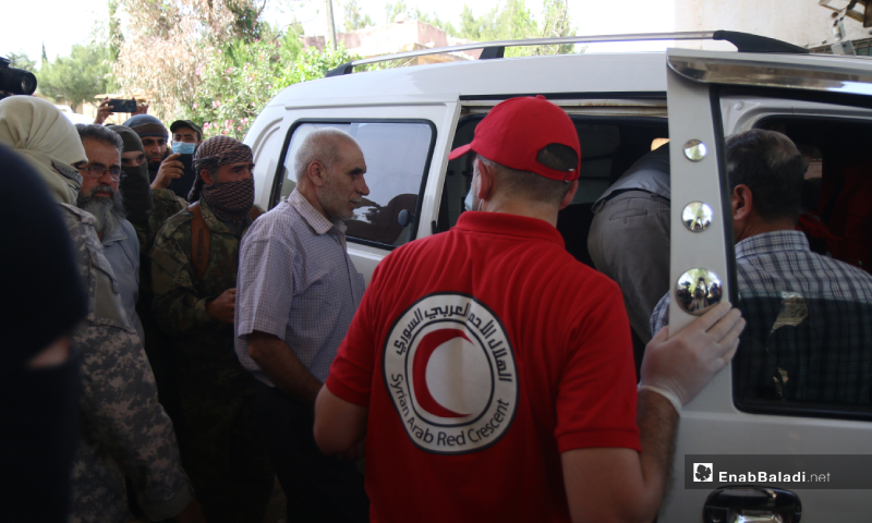 The prisoners of the Syrian regime forces getting into the vehicle during the prisoners' exchange process between the Syrian regime and the HTS – 16 May 2020 (Enab Baladi / Yousef Ghuraibi)