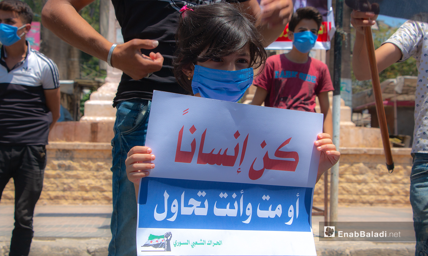 A child holding a sign at a protest stand in Idlib city's Clock Square – 10 July 2020 (Enab Baladi / Anas al-Khouli)