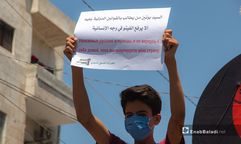 A child lifting a sign directed to the Russian president, Vladimir Putin – 10 July 2020 (Enab Baladi / Anas al-Khouli)