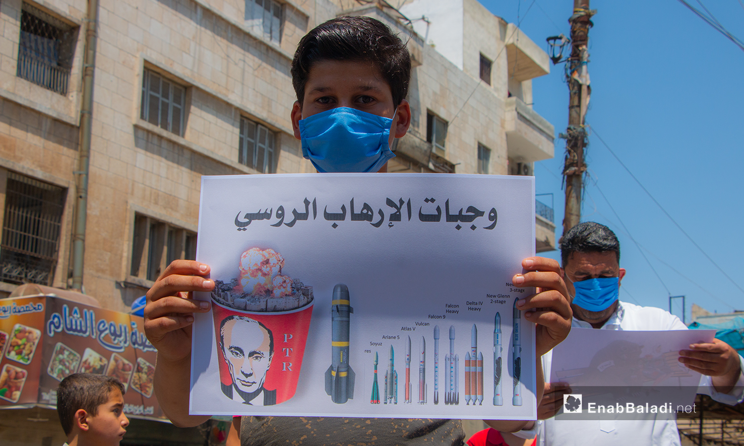 A child holding a sign on the missiles' types that targeted the Syrian people – 10 July 2020 (Enab Baladi / Anas al-Khouli)