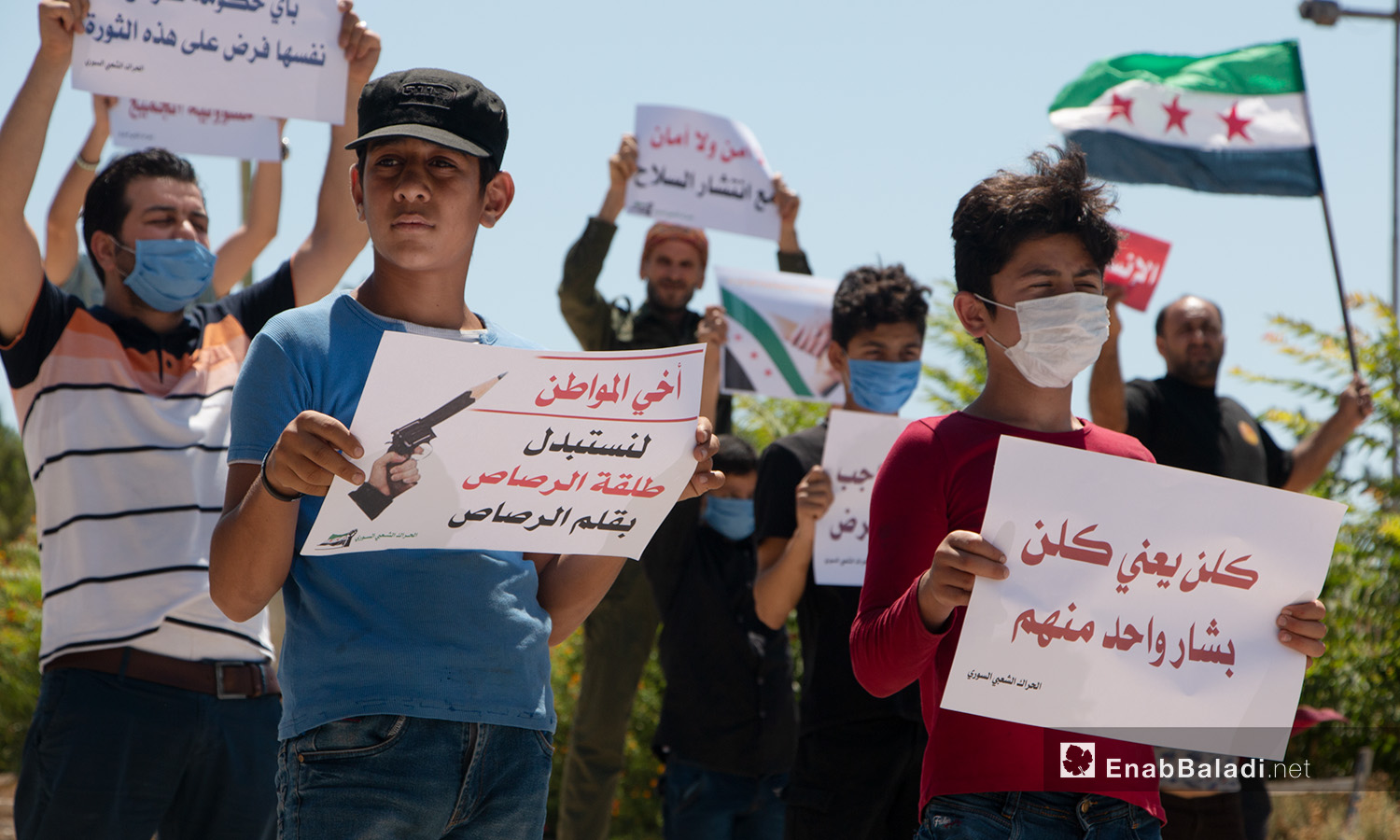 Children and young men carrying signs during a protest stand in Idlib city – 17 July 2020 (Enab Baladi / Anas al-Khouli)