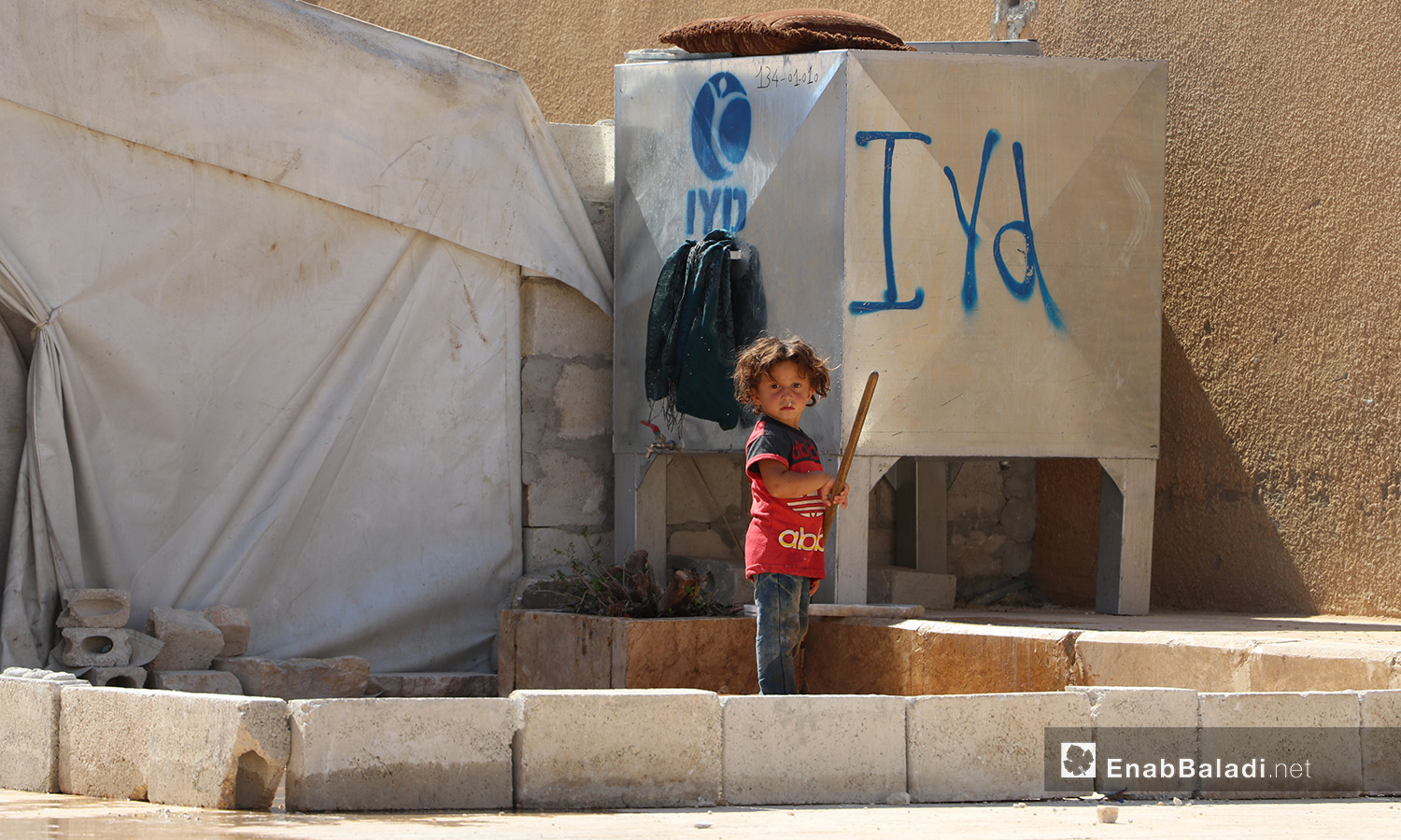 A child standing in front of a water tank in Qibtan Camp near Akhtarin town in northern Aleppo countryside – 17 July 2020 (Enab Baladi / Asim Melhem)