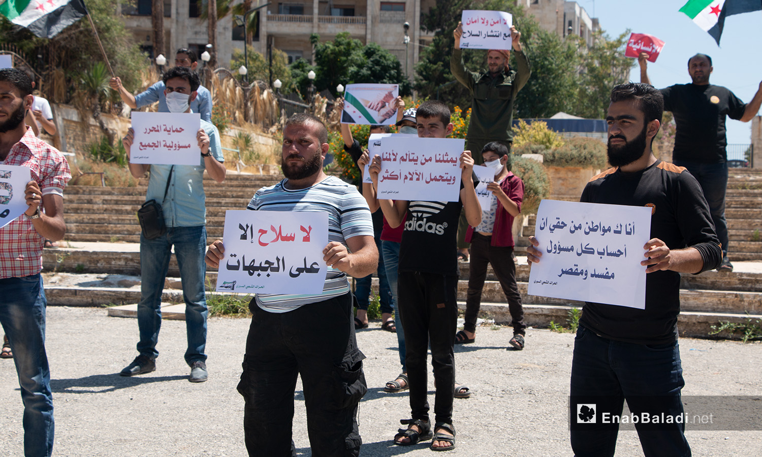 A group of young men carrying signs during a protest stand in Idlib city – 17 July 2020 (Enab Baladi / Anas al-Khouli)
