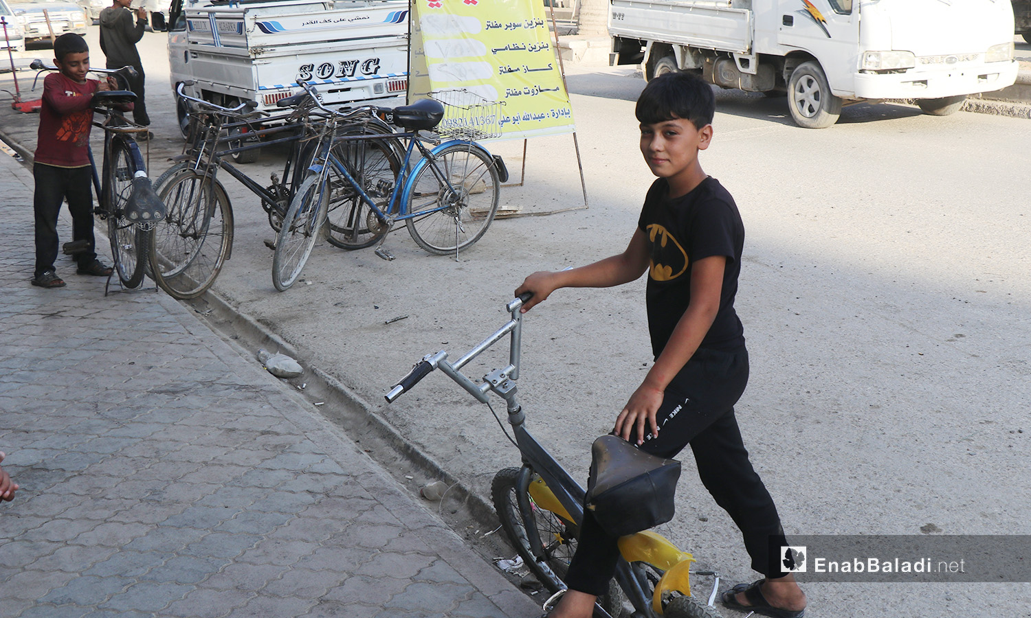 A child with his bicycle in al-Raqqa city – 26 July 2020 (Enab Baladi / Abdul Aziz Saleh)