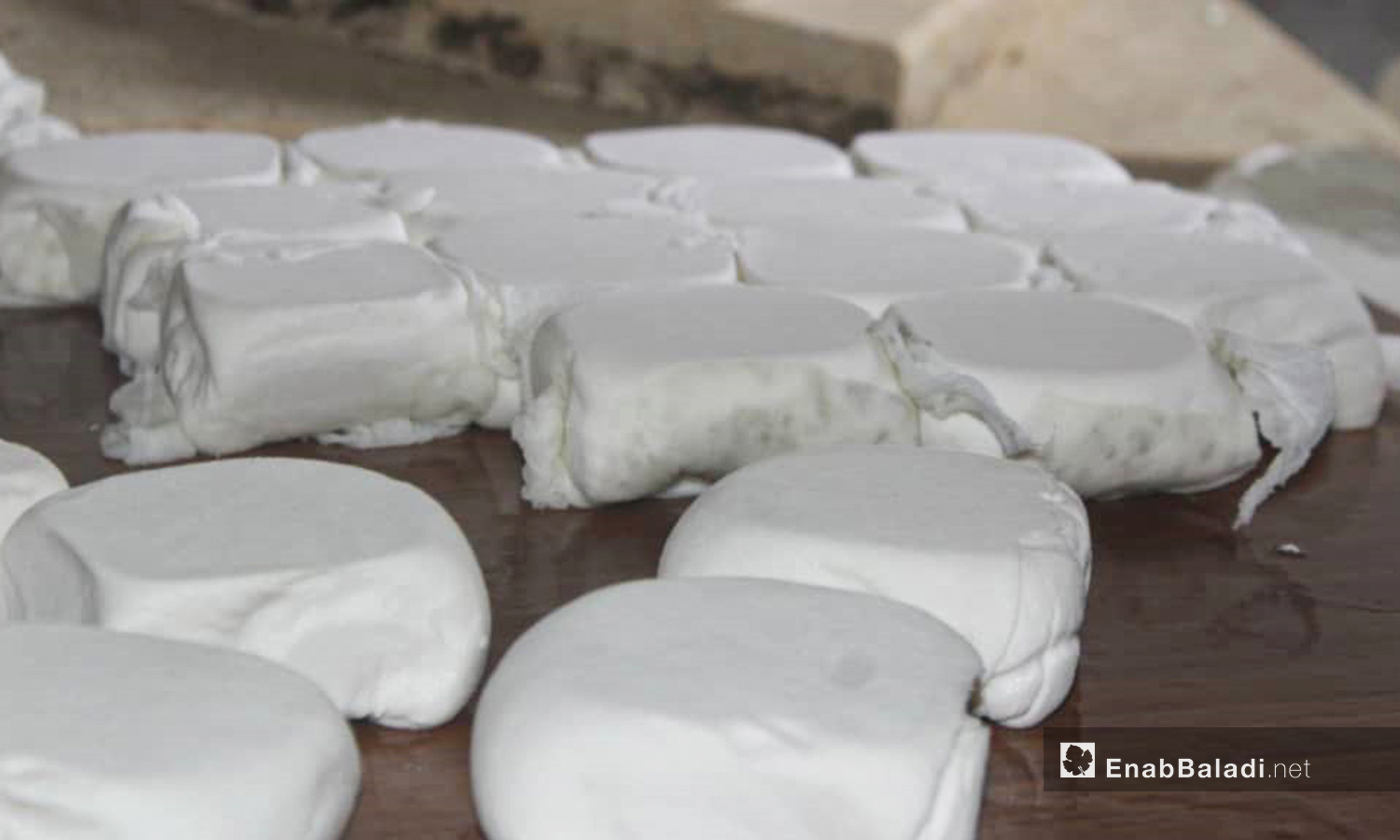 The stage of removing cheese from the plunger in the cheese-making process in al-Dana city of northern Idlib countryside – 04 June 2020 (Enab Baladi / Shadia al-Taataa)