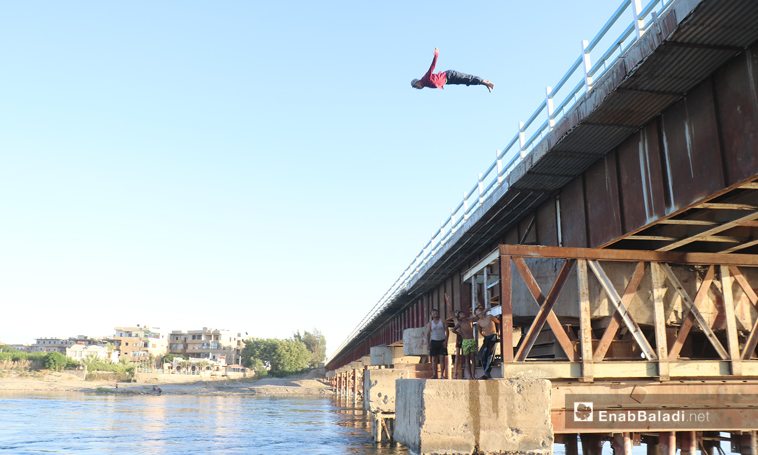 A young man jumping from the top of a bridge over the Euphrates River in al-Raqqa province – 24 July 2020 (Enab Baladi / Abdul Aziz Saleh)